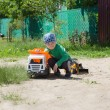 The boy plays with machines on the street — Stock Photo #77044557