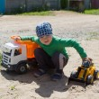 The boy plays with machines on the street — Stock Photo #77045167