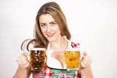 Woman posing in dirndl dress against a white wall. — Stock Photo
