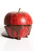 Apple with dark chocolate oozing out. — Stock Photo