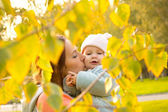 Young mother with her children in the park autumn — Stock Photo