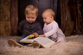 Children on a fluffy carpet with book — Stock Photo