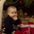 Baby girl with gifts under Christmas tree — Stock Photo #53723893