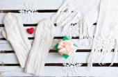 White mittens, scarf and gift on a wooden plank background with copy space — Stock fotografie