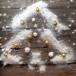 Stylized design Christmas tree with xmas balls and snow on wooden background — Stock Photo #60863465