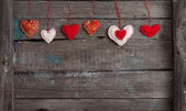 Lot of hearts on wooden background — Stock Photo