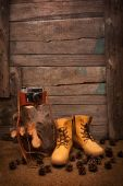 Still life with boots and retro camera on wooden background — Стоковое фото