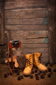 Still life with boots and retro camera on wooden background — Stock fotografie