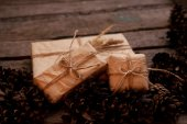 Vintage gift on wooden background with cones — Stock Photo