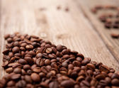 Coffee beans and cup on wooden background — Stock Photo