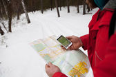 Phone and map in the hands of men hiking winter forest — Stock Photo