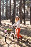 Beautiful young woman on bike in sunny park — Foto de Stock