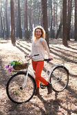 Beautiful young woman on bike in sunny park — Stok fotoğraf