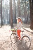 Beautiful young woman on bike in sunny park — ストック写真