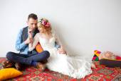 Barefooted bride and groom sitting on floor — Stock Photo