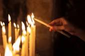 Allumer des bougies dans une église femme — Photo