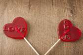Red candies with heart shaped topping on wooden background — Φωτογραφία Αρχείου