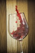 Red wine into the glass with wooden background — Stock Photo