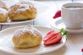 Fluffy bun of puff pastry with strawberry filling and coffee — Stock Photo