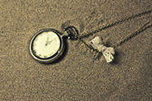 Antique clock in the sand — Stock Photo