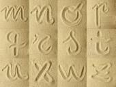 Alphabet handwritten in the sand — Stock Photo