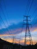 High voltage power pylons in sun set — 图库照片