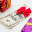 Stack of dollars with red bow and gift boxes — Stock Photo #55460115