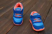 Pair of blue sporty shoes for kid on wood — Foto de Stock
