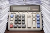 Pile of documents on desk stack up high with calculator on office desk — Stock Photo