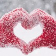 Woman making heart symbol with snowy hands — Stock Photo #62399339