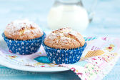 Close-up of two homemade orange muffins with a jug of milk, sele — Stock Photo