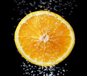 Half a fresh orange in water on a black background with air bubb — Stock Photo