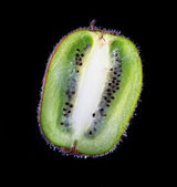 Half a fresh kiwi in water on a black background with air bubble — Stock Photo