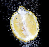 Half a fresh lemon in water on a black background with air bubbl — Stock Photo