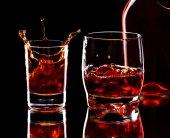 стекло и бутылка виски с всплеск на темном фоне, селе — Стоковое фото