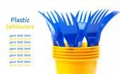 Brillanti stoviglie di plastica, bicchieri e forchette su sfondo bianco, se — Foto Stock