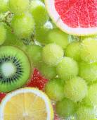 Fruit: green grapes, kiwi, lemon and grapefruit in the water on — Stock Photo