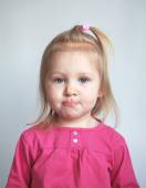 Funny portrait of little cute girl with blue eyes in a pink dres — Stock Photo