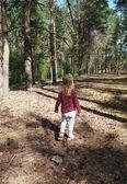 Niña rubia intrépidamente camina solo por el bosque — Foto de Stock