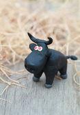Plasticine world - little homemade black bull with red eyes stan — Stock Photo