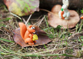 Plasticine world - small homemade squirrel holds the chanterelle — Stock Photo