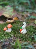 Plasticine world - little homemade white rabbit with carrot sitt — Stock Photo
