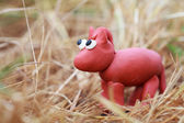 Plasticine world - little homemade red horse stands in the hay,  — 图库照片