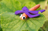 Plasticine world - little homemade orange dragonfly with purple — Stock Photo