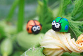 Plasticine world - little homemade green and orange ladybugs sit — Fotografia Stock