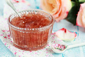 Small jam dish with rose petal jam on a blue wooden table with f — Stock Photo