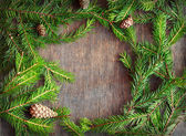 Christmas fir tree with cones on a wooden background, selective  — Photo