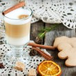 Hot coffee with milk in a glass on a wooden table with pieces of — Stock Photo #57633235