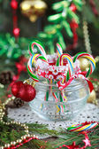 Multicolored candy canes in the glass jar with red balls between — Stock Photo
