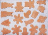 Christmas gingerbread cookies from fresh dough on baking paper:  — Foto de Stock